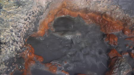 volcanology : Natural volcanic hot springs splashing of boiling water from hole. Geothermal field on active Mutnovsky Volcano - active travel destinations to observe volcanoes activity in Kamchatka Peninsula.