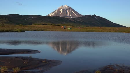 eurasia : Stunning autumn volcano landscape of Kamchatka Peninsula at sunset: scenery evening view of cone Vilyuchinsky Volcano, mountain tourist camping and reflection of mountains in picturesque alpine lake. Stock Footage
