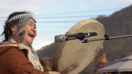 tambor : KAMCHATKA PENINSULA, RUSSIA - NOV 4, 2018: Woman in national clothing indigenous inhabitants Kamchatka beats tambourine and sings. Concert, celebration of Koryak national holiday Hololo (Day of Seal).
