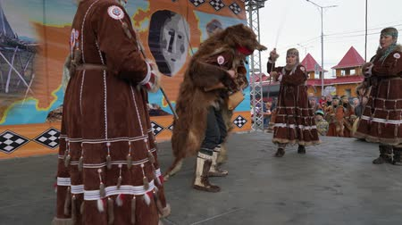 ethnography : KAMCHATKA PENINSULA, RUSSIA - NOV 4, 2018: Man in bearskin dances with women in national clothing indigenous inhabitants Kamchatka. Celebration of Koryak national ritual holiday Hololo (Day of Seal). Stock Footage