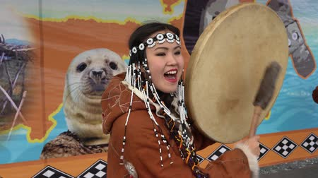 tambourine : KAMCHATKA PENINSULA, RUSSIA - NOV 4, 2018: Young woman in national clothing indigenous inhabitants Kamchatka beats tambourine and sings. Celebration of Koryak national holiday Hololo (Day of Seal).