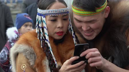 ethnography : KAMCHATKA PENINSULA, RUSSIA - NOV 4, 2018: Young woman dancer in national clothing indigenous inhabitants Kamchatka reads messages in smartphone, and young man looking into her phone.