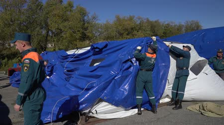 uzak : KAMCHATKA PENINSULA, RUSSIA - OCT 2, 2018: Group of rescuers Kamchatka Rescue Center Emercom of Russia setting up an army field tent, deploy campground on windy day. All-Russian civil defense training
