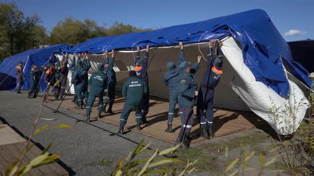 rescuer : KAMCHATKA PENINSULA, RUSSIA - OCT 2, 2018: Group of rescuers Kamchatka Rescue Center Emercom of Russia setting up an army field tent, deploy campground on windy day. All-Russian civil defense training