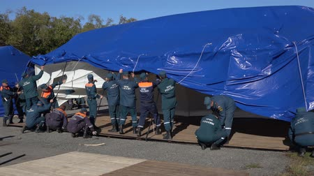 daleko : KAMCHATKA PENINSULA, RUSSIA - OCT 2, 2018: Group of rescuers Kamchatka Rescue Center Emercom of Russia setting up an army field tent, deploy campground on windy day. All-Russian civil defense training