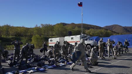 rescuer : KAMCHATKA PENINSULA, RUSSIA - OCT 3, 2018: Training, acceptance of tests by rescuers according to standard - Putting on an all-arms protective kit and filtering gas mask. Kamchatka Rescue Center Emercom of Russia. All-Russian civil defense training. Stock Footage