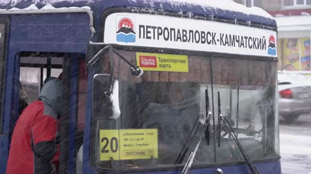 porta : PETROPAVLOVSK CITY, KAMCHATKA PENINSULA, RUSSIA - DECEMBER 26, 2018: winter city life during blizzard (snowstorm) - passenger city bus.