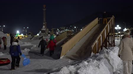 petropavlovsk : PETROPAVLOVSK KAMCHATSKY CITY, KAMCHATKA PENINSULA, RUSSIA - DEC 30, 2018: Childrens ride from the winter ice slide located in snowy town Happy New Year in center of capital Kamchatka Territory. Stock Footage