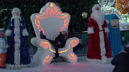 poloostrov : PETROPAVLOVSK KAMCHATSKY CITY, KAMCHATKA, RUSSIAN FAR EAST - DEC 31, 2018: Children and adults - residents of Kamchatka Peninsula photographed sitting on throne near the citys New Year tree.
