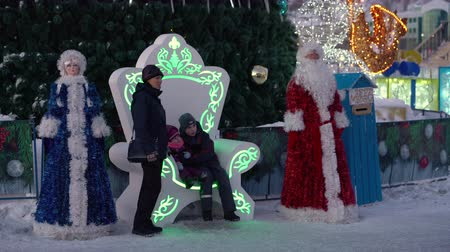petropavlovsk : PETROPAVLOVSK KAMCHATSKY CITY, KAMCHATKA, RUSSIAN FAR EAST - DEC 31, 2018: Children and adults - residents of Kamchatka Peninsula photographed sitting on throne near the citys New Year tree.