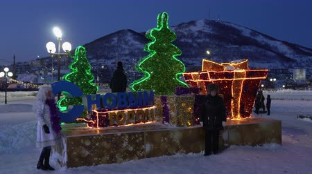 night scape : PETROPAVLOVSK KAMCHATSKY CITY, KAMCHATKA PENINSULA, RUSSIA - DEC 31, 2018: People take pictures at festive composition Happy New Year located in snowy town in center of capital Kamchatka Territory. Stock Footage