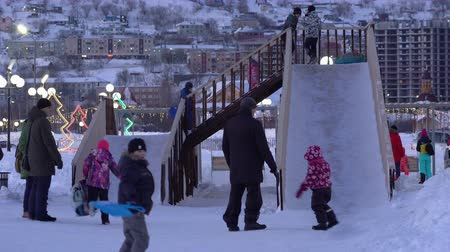 petropavlovsk : PETROPAVLOVSK KAMCHATSKY CITY, KAMCHATKA PENINSULA, RUSSIAN FAR EAST - DEC 31, 2018: Children ride from winter ice slide located in snowy town Happy New Year in center of capital Kamchatka Territory. Stock Footage