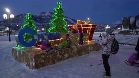 night scape : PETROPAVLOVSK KAMCHATSKY CITY, KAMCHATKA, RUSSIAN FAR EAST - JAN 1, 2019: Night view of people take pictures at celebration composition Happy New Year located in snowy town in capital Kamchatka Peninsula. Stock Footage