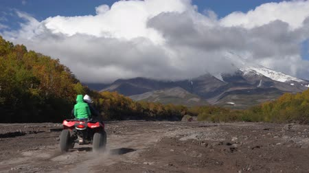 daleko : KAMCHATKA PENINSULA, RUSSIAN FAR EAST - SEP 23, 2018: Quadracycle driving on mountain road on volcanic dry river in direction of active Koryaksky Volcano - popular travel destinations.