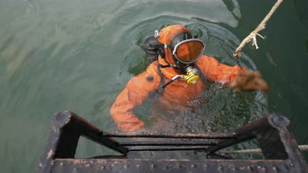 gangplank : Professional scuba diver in an orange diving suit ducking into ocean to carry out repair diving work of ship underwater. Kamchatka Peninsula, Pacific Ocean, Russian Far East.