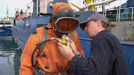 compensar : KAMCHATKA PENINSULA, RUSSIA - 5 SEP, 2018: Sailor helps diver to put on vest with compressed air cylinders and connects breathing hose to diving mask before diving into cold water of Pacific Ocean.
