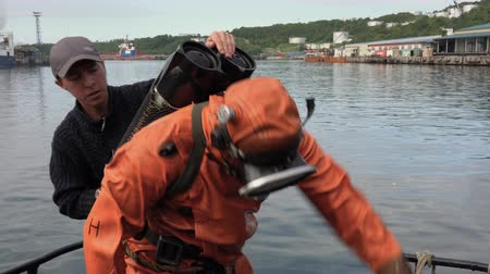 compensar : KAMCHATKA PENINSULA, PACIFIC OCEAN, RUSSIAN FAR EAST - 5 SEP, 2018: Sailor removes black gas cylinder (air balloon) from professional scuba diver in orange diving suit after long work underwater.