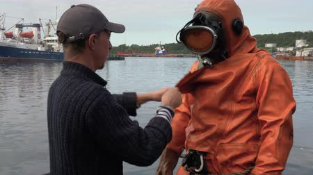 compensar : KAMCHATKA PENINSULA, RUSSIAN FAR EAST - 5 SEP, 2018: Sailor unties, helps to take off dry orange diving suit to professional scuba diver after diving into cold water of Pacific Ocean.