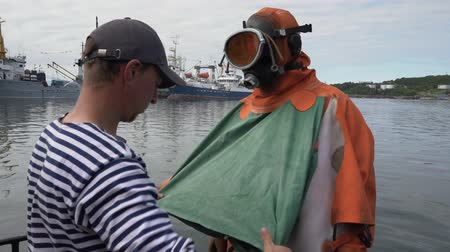 daleko : KAMCHATKA PENINSULA, RUSSIAN FAR EAST - 5 SEPTEMBER, 2018: Sailor tying, helps to put on dry orange diving suit to professional scuba diver before diving into cold water of Pacific Ocean.