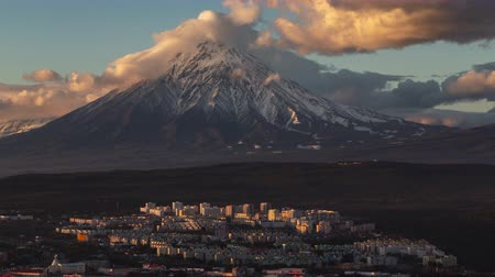 petropavlovsk : Kamchatka Peninsula time lapse: evening top view of stunning cityscape of Petropavlovsk-Kamchatsky City on background clouds drifting across sky and cone of active Koryaksky Volcano. Kamchatka Region, Russian Far East, Eurasia.