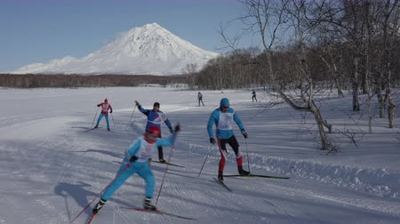 ski run : KAMCHATKA PENINSULA, RUSSIAN FAR EAST - FEBRUARY 9, 2019: All-Russian Federation Mass Ski Race - Ski Track of Russia. Group of skiers running along winter ski track in forest on background of volcano.