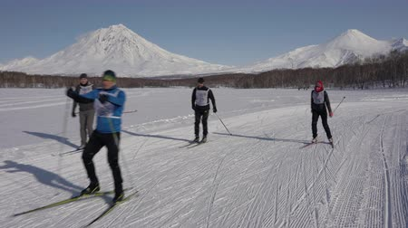 ski run : KAMCHATKA PENINSULA, RUSSIAN FAR EAST - FEB 9, 2019: Group of skiers running along winter ski track on background of volcanoes on sunny day. All-Russia mass ski race - Ski Track of Russian Federation.