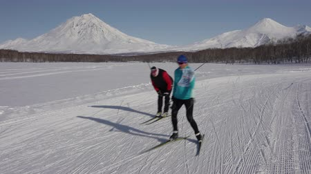 ski run : KAMCHATKA PENINSULA, RUSSIA - FEBRUARY 9, 2019: All-Russia Mass Ski Race - Ski Track of Russian Federation. Group of skiers running along winter ski track on background of volcanoes on sunny day.