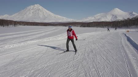 petropavlovsk : KAMCHATKA, RUSSIAN FAR EAST - FEB 9, 2019: All-Russian Federation Mass Ski Race - Ski Track of Russia. Group of skiers running along winter ski track on background of volcanoes on sunny weather. Stock Footage
