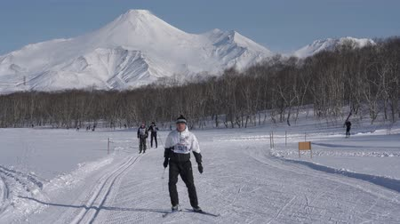ski run : KAMCHATKA PENINSULA, RUSSIAN FAR EAST - FEBRUARY 9, 2019: Group of skiers running along winter ski track on background of Avacha Volcano. All-Russia mass ski race - Ski Track of Russian Federation.