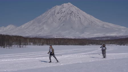 ski run : KAMCHATKA PENINSULA, RUSSIAN FAR EAST - FEBRUARY 9, 2019: Group of skiers running along winter ski track on background of Koryaksky Volcano. All-Russia mass ski race - Ski Track of Russian Federation. Stock Footage