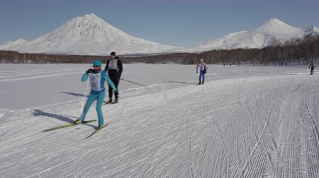 ski run : KAMCHATKA, RUSSIAN FAR EAST - FEB 9, 2019: All-Russian Federation Mass Ski Race - Ski Track of Russia. Group of skiers running along winter ski track on background of volcanoes on sunny weather. Stock Footage