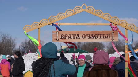 креп : YELIZOVO CITY, KAMCHATKA PENINSULA, RUSSIA - MAR 10, 2019: People photographed near Gate of Happiness during Maslenitsa - Russian religious, folk holiday, celebrated during last week before Great Lent Стоковые видеозаписи