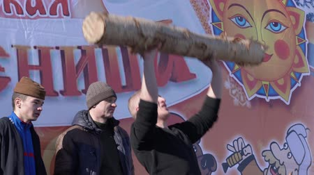 festividades : YELIZOVO CITY, KAMCHATKA PENINSULA, RUSSIA - MARCH 10, 2019: Man raises birch log over his head - Russian fun during folk festivities on Maslenitsa - religious, folk holiday, celebrated during last week before Great Lent.
