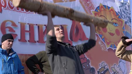 креп : YELIZOVO CITY, KAMCHATKA PENINSULA, RUSSIA - MARCH 10, 2019: Russian fun - man raises birch log over his head during folk festivities on Maslenitsa - religious, folk holiday, celebrated during last week before Great Lent.