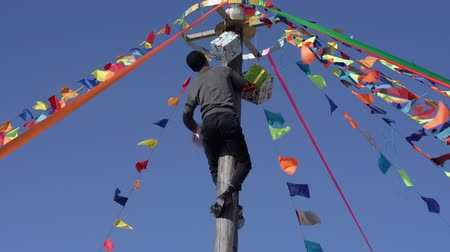 festividades : KAMCHATKA PENINSULA, RUSSIAN FAR EAST - MARCH 10, 2019: Old Russian tradition fun - young man without assistance, any technical devices climbing to top of wooden pole for prizes and gifts. Russian folk festivities Maslenitsa - religious, holiday.