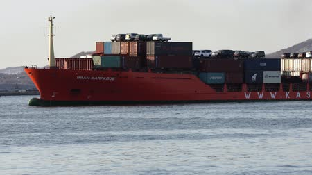 daleko : KAMCHATKA PENINSULA, RUSSIA - 2 MAY, 2019: Container Ship Ivan Kapralov (KASCO) transportation containers and cars across Pacific Ocean from Vladivostok Sea Port to Petropavlovsk-Kamchatsky Sea Port.