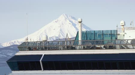 upper peninsula : KAMCHATKA PENINSULA, RUSSIAN FAR EAST - 2 MAY, 2019: Deserted upper deck of luxury passenger expedition Cruise Liner Celebrity Millennium (Celebrity Cruises) on background majestic cone of volcano.