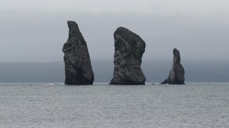 eurasia : Kamchatka Peninsula seascape: picturesque zoom in view of rocky islands in sea - Three Brothers Rocks in Avacha Bay in Pacific Ocean on cloudy gloomy day. Eurasia, Russian Far East, Kamchatka Territory.