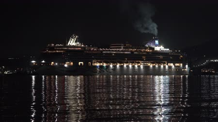 night scape : PACIFIC OCEAN, KAMCHATKA PENINSULA, RUSSIA - 10 MAY, 2019: Dark night view of Cruise Liner Norwegian Jewel reverse sailing in Sea Port Petropavlovsk-Kamchatsky City. Porthole lights reflection in sea.