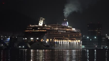 petropavlovsk : KAMCHATKA PENINSULA, RUSSIA - 10 MAY, 2019: Night view of Cruise Liner Norwegian Jewel sailing on background mountains coastline Sea Port Petropavlovsk-Kamchatsky. Porthole lights reflection in ocean.