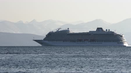 személyszállító hajó : PACIFIC OCEAN, KAMCHATKA PENINSULA, RUSSIAN FAR EAST - 13 MAY, 2019: Passenger Expedition Cruise Liner Viking Orion (Viking Ocean Cruises) sailing in ocean on background of mountains coastline.