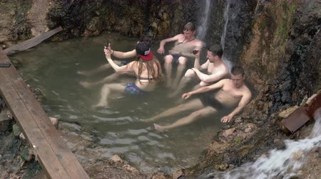 molas : KAMCHATKA PENINSULA, RUSSIA - JUNE 12, 2019: Group of young travelers take therapeutic, medicinal baths in outdoor pool natural hot springs with geothermal mineral water having balneological properties