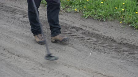 screening : Treasure hunter walking on country road, holding electronic metal detector - scanning ground of road in search of metal objects. Use metal detector in action in countryside, field conditions in summer Stock Footage