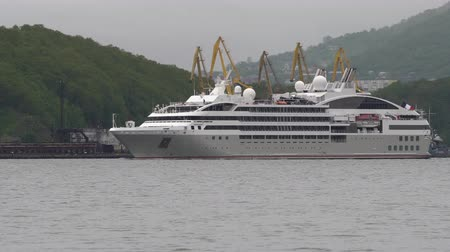 uzak : PACIFIC OCEAN, KAMCHATKA PENINSULA, RUSSIAN FAR EAST - 24 JUNE, 2019: Passenger Cruise Liner Le Soleal (Compagnie du Ponant) sailing on background mountains coastline Sea Port Petropavlovsk-Kamchatsky Stok Video