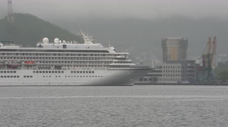 uzak : PACIFIC OCEAN, KAMCHATKA PENINSULA, RUSSIA - 8 JULY, 2019: Japanese Cruise Liner Asuka II (NYK CRUISES CO., LTD.) reverse sailing on background mountains coastline Sea Port Petropavlovsk-Kamchatsky. Time lapse Stok Video