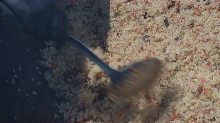 cop : Cooking pilaf in cauldron, mixing pilaf holding kitchen spoon. Asian traditional culinary dish - pilaf. Ingredients: rice, meat, vegetables (carrot, onion), spices and fat. National Eastern tasty food