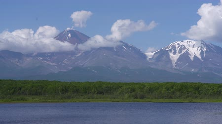daleko : Summer landscape of Kamchatka Peninsula: view of cone active Avacha Volcano, alpine lake and clouds drifting across blue sky near mountains in sunny weather. Travel destinations in Russian Far East. Dostupné videozáznamy