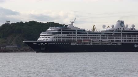 quest : PACIFIC OCEAN, KAMCHATKA PENINSULA, RUSSIAN FAR EAST - 15 AUGUST, 2019: Passenger Expedition Cruise Liner Azamara Quest sailing on background mountains coastline Sea Port Petropavlovsk-Kamchatsky.