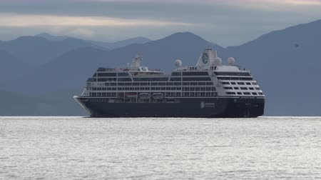 quest : PACIFIC OCEAN, KAMCHATKA PENINSULA, RUSSIAN FAR EAST - 15 AUGUST, 2019: Expedition Passenger Cruise Liner Azamara Quest sailing in sea on background of mountains coastline, cloudy sky in evening.
