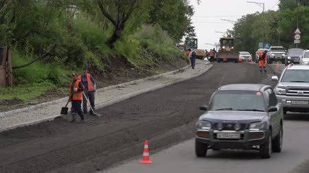 roadwork : Time lapse: road construction workers laying asphalt, road repairing, asphalt pavement works on city road, in consequence of which stopping traffic road. Petropavlovsk City, Russia - August 27, 2019